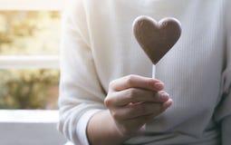 Kobieta pokazuje czekoladę w kierowym kształcie valentine, miłość, romantyczna Zdjęcie Royalty Free