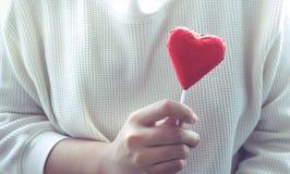 Kobieta pokazuje czerwoną czekoladę w kierowym kształcie valentine Obrazy Royalty Free