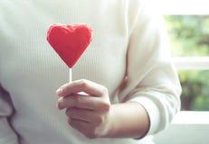 Kobieta pokazuje czerwoną czekoladę w kierowym kształcie valentine, miłość Obrazy Royalty Free