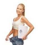Kobieta pokazuje dużych spodnia i trzyma waży Zdjęcia Stock