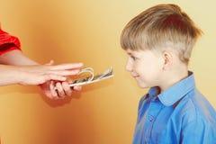 Kobieta pokazuje dziecko pieniądze i go, zazdrości przy dolar, z pragnieniem dostawać bogactwo zdjęcia stock