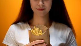 Kobieta pokazuje francuzów dłoniaki i przejada się, ryzyko otyłość, wysoki kaloria posiłek obrazy stock
