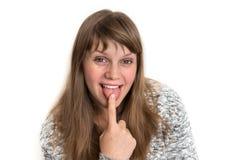 Kobieta pokazuje jęzor i dotyka je z jeden palcem fotografia stock