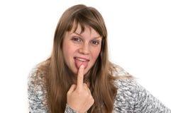 Kobieta pokazuje jęzor i dotyka je z jeden palcem zdjęcie stock