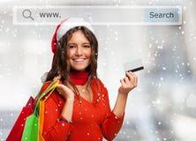 Kobieta pokazuje jej kredytową kartę podczas gdy robiący zakupy przed bożymi narodzeniami Obraz Stock