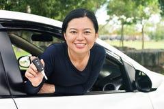 Kobieta pokazuje klucze jej nowy samochód zdjęcie stock