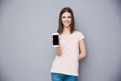 Kobieta pokazuje pustego smartphone ekran obrazy royalty free