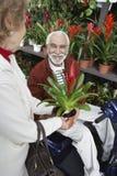 Kobieta Pokazuje Puszkującego kwiatu starsza osoba mężczyzna W ogródzie botanicznym zdjęcie stock