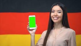 Kobieta pokazuje smartphone z zieleń ekranem, niemiec flaga na tle, app zbiory