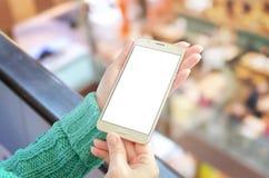 Kobieta pokazuje złocistego mądrze telefon z odosobnionym, białym, pustym pokazem dla app promoci mockup, Zdjęcie Stock