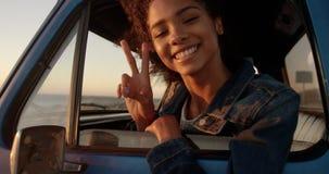Kobieta pokazuje zwycięstwo podpisuje wewnątrz furgonetkę przy plażą 4k zbiory wideo