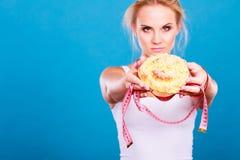 Kobieta poleca non cukrową dietę trzyma słodką babeczkę Zdjęcie Royalty Free