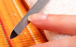 Kobieta polerowniczy paznokcie z gwóźdź kartoteką Fotografia Stock