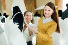 Kobieta pomaga panny młodej w wybierać bridal togę Zdjęcie Royalty Free