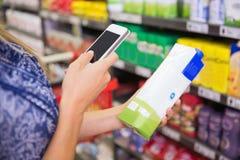 Kobieta porównuje cenę karton mleko z jej telefonem Zdjęcie Royalty Free