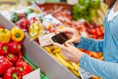 Kobieta porównuje warzywa z smartphone obrazy royalty free