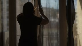 Kobieta poszerza zasłony pozwala jaskrawych promienie ciepły lata słońce w pokój zbiory