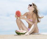 Kobieta pozuje na plaży i je arbuza fotografia royalty free