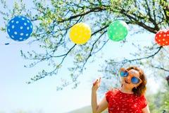Kobieta pozuje w czerwieni sukni i dużych śmiesznych słońc szkłach na ogródzie - balony obrazy royalty free