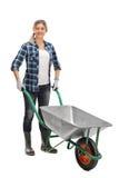 Kobieta pozuje z pustym wheelbarrow fotografia royalty free