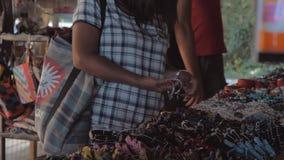 Kobieta pr?buje dalej barwi? bransoletki w azjatykcim ulicznym rynku Sprzeda? bransoletki w rynku zbiory