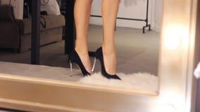 kobieta próbuje dalej czarnego zamszowy szpilki wysoką piętę cieki kroczą na białym puszystym dywanie odbijający wizerunek w zbiory