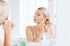 Kobieta próbuje na kolczyku patrzeje łazienki lustro Obraz Royalty Free