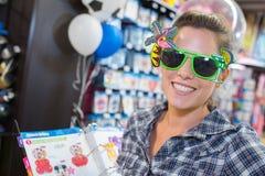 Kobieta próbuje odkrywczość okulary przeciwsłonecznych w sklepie obrazy royalty free