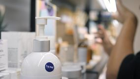 Kobieta Próbuje tester kiści Sunscreen Bodt śmietankę na ręki skórze w kosmetyka supermarkecie w zakupy centrum handlowym 4K zbiory