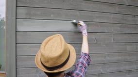 Kobieta pracownik maluje drewnianą domową zewnętrzną ścianę z paintbrush i drewnianym ochronnym kolorem zdjęcie wideo