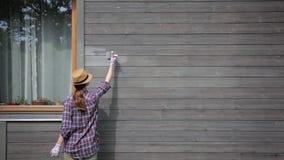 Kobieta pracownik maluje drewnianą domową zewnętrzną ścianę z paintbrush i drewnianym ochronnym kolorem zbiory