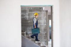 Kobieta pracownik z narzędziowym pudełkowatym odprowadzenie puszkiem schodki na budowie zdjęcie royalty free
