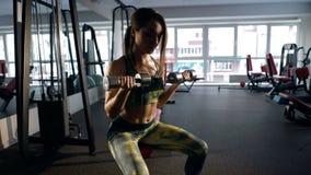 Kobieta pracuje na jej bicepsach w gym Zdjęcia Royalty Free