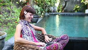 Kobieta pracuje na jej laptopu obsiadaniu w karle przy poolside, Bali wyspa zbiory