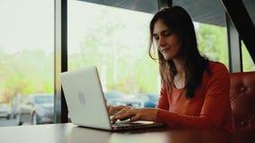 Kobieta pracuje na laptopie, duma, ono uśmiecha się w kawiarni zbiory