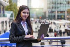 Kobieta pracuje na laptopie outdoors w Canary Wharf, UK obraz stock