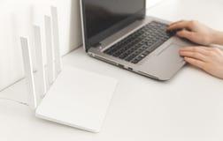 Kobieta pracuje na laptopie w domu Biały wifi router na białym tle minimalista obraz royalty free