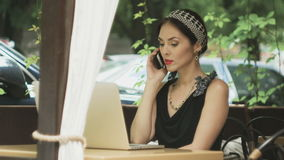 Kobieta pracuje na laptopie w kawiarni i odpowiada wezwanie, selekcyjna ostrość zdjęcie wideo