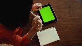 Kobieta pracuje na pastylce, nakreślenia w notatniku zielony ekran zbiory
