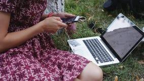 Kobieta pracuje na trawie z laptopem i smartphone zbiory wideo
