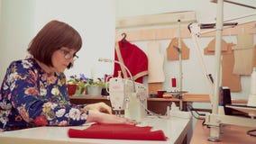 Kobieta pracuje przy szwalną maszyną w studiu zbiory