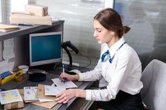 Kobieta pracuje przy urzędem pocztowym obraz royalty free
