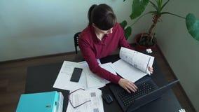 Kobieta pracuje z dokumentami i laptopem w biurze zbiory