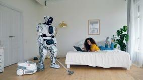 Kobieta pracuje z laptopem podczas gdy droid robi próżniowy czyścić Cyborga i istoty ludzkiej pojęcie zdjęcie wideo