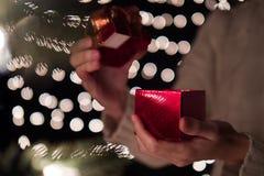 Kobieta prezenta otwarty czerwony Bożenarodzeniowy pudełko z bokeh zaświeca tło Obraz Stock