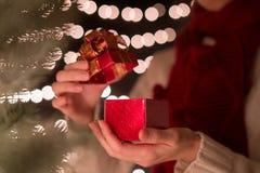 Kobieta prezenta otwarty czerwony Bożenarodzeniowy pudełko z jarzeniowym bokeh zaświeca tło Fotografia Royalty Free