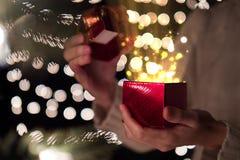 Kobieta prezenta otwarty czerwony Bożenarodzeniowy pudełko z promieniem magii światło na bokeh zaświeca tło Fotografia Royalty Free