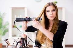 Kobieta projektuje jej włosy z hairdryer obraz stock