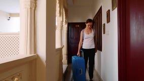Kobieta przechodzi w hotel i stacza si? walizk? jej pok?j Frontowy widok zbiory wideo