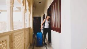 Kobieta przechodzi w hotel i stacza si? walizk? jej pok?j obraz stock